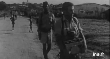 Michel Honorin, en reportage au Soudan, en juillet 1965, suivi de très près par des gardes