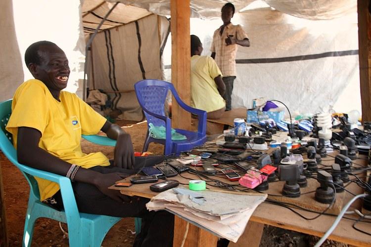 """Dans un camp de réfugiés, au Soudan du Sud, une """"boutique"""" pour recharger les téléphones portables et les ampoules. (CC) Oxfam International"""